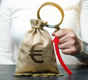 La mano femenina sostiene la lupa sobre bolso y para arriba flecha del dinero Análisis de concepto de beneficios y del presupuest fotografía de archivo libre de regalías
