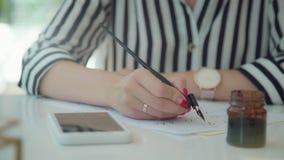 La mano femenina sostiene la pluma para la caligrafía, mira ejemplo en Internet almacen de metraje de vídeo