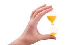 La mano femenina sostiene un arena-vidrio Imágenes de archivo libres de regalías