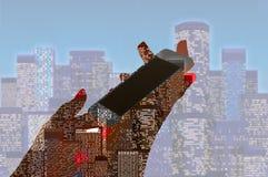 La mano femenina sostiene un teléfono con una ciudad de la noche Fotos de archivo
