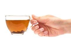 La mano femenina sostiene una taza de té Aislado en el fondo blanco Imagen de archivo
