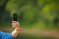 La mano femenina toma imágenes con el teléfono elegante móvil Imagen de archivo