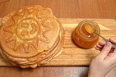 La mano femenina toma la miel de la cuchara del tarro de cristal y pone las crepes foto de archivo