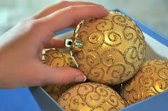 La mano femenina toma una bola de la Navidad de una caja Fotografía de archivo libre de regalías