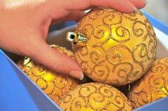 La mano femenina toma una decoración del árbol de navidad de una caja Imágenes de archivo libres de regalías