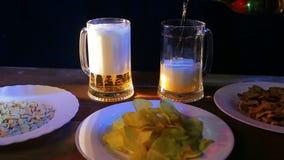 La mano femenina vierte la cerveza en una barra en las tazas transparentes grandes metrajes