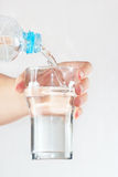 La mano femenina vierte el agua mineral en un vidrio de la botella Fotografía de archivo libre de regalías
