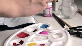 La mano femenina vierte la pintura rosada en una paleta, toma un cepillo, lo aclara en un vaso de agua, clavadas él en pintura ilustración del vector