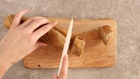 La mano femminile affetta le baguette fresche della segale stock footage