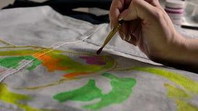 La mano femminile applica la pittura rosa su tessuto con un modello facendo uso di una spazzola stock footage