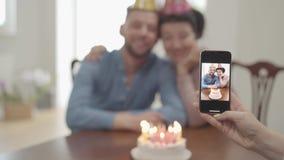 La mano femminile che fa una foto sul cellulare della donna matura sorridente felice che abbraccia con il nipote adulto, sia dent video d archivio