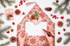 La mano femminile che scrive una lettera a Santa sul fondo con i regali di Natale, abete di festa si ramifica, pigne, decorazioni Fotografia Stock