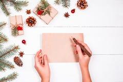 La mano femminile che scrive una lettera a Santa sul fondo con i regali di Natale, abete di festa si ramifica, pigne, Disposizion Immagini Stock Libere da Diritti
