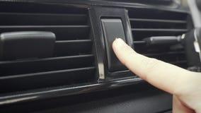 La mano femminile che spinge le luci di emergenza si abbottona in automobile archivi video