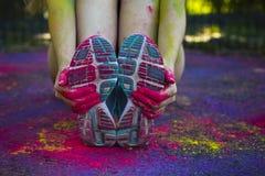 La mano femminile che tiene le sue scarpe da tennis ha coperto il holi della pittura Fotografia Stock