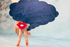 La mano femminile con due dita giù sorride e labbra rosse su un fondo blu e sui pensieri regionali immagine stock