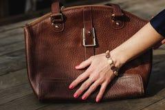 La mano femminile con il braccialetto tiene una borsa di cuoio marrone Immagini Stock
