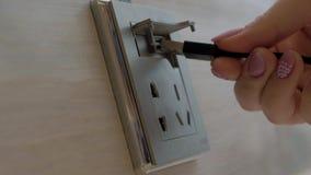 La mano femminile inserisce il cavo alla console di potere dello scrittorio Caricare la batteria del telefono cellulare alla staz archivi video