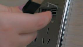 La mano femminile inserisce il cavo alla console di potere dello scrittorio Caricare la batteria del telefono cellulare alla staz stock footage