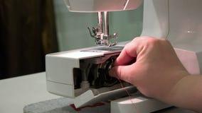 La mano femminile inserisce la cassa della bobina con il perno nel piatto dell'ago stock footage