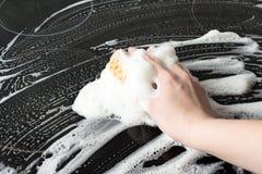 La mano femminile lava la cucina elettrica Schiuma porosa gialla del sapone e della spugna Concetto di servizio di pulizia Immagine Stock Libera da Diritti