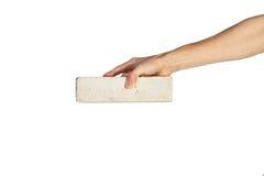 La mano femminile prende il mattone bianco Fotografia Stock