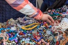 La mano femminile prende le perle da un contatore con molte perle Fotografia Stock Libera da Diritti