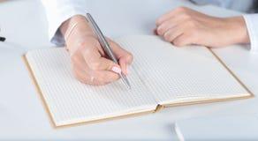 La mano femminile scrive con una penna in un taccuino del diario Fotografia Stock