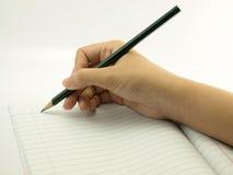 La mano femminile scrive il fondo di bianco del taccuino Fotografia Stock