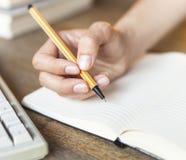 La mano femminile scrive in un diario del taccuino lavoro Immagine Stock Libera da Diritti