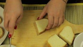 La mano femminile spalma il burro bianco per le canape di burro stock footage