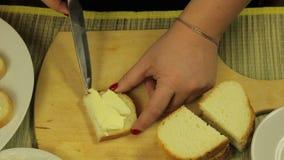 La mano femminile spalma il burro bianco per le canape di burro video d archivio