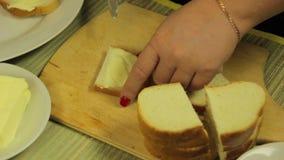 La mano femminile spalma il burro bianco per le canape di burro archivi video