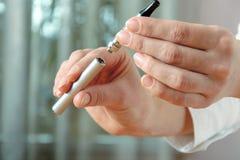 La mano femminile stacca la parte della sigaretta elettronica Fotografia Stock