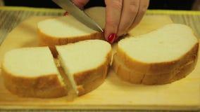 La mano femminile taglia il pane bianco per le canape Il piano medio stock footage