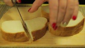 La mano femminile taglia il pane bianco per le canape Rivestimenti di tempo video d archivio