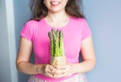 La mano femminile tiene il pacco di asparago verde Concetto dei vegani, dei vegetariani e dell'alimento sano Fotografia Stock Libera da Diritti