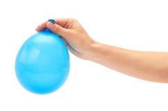 La mano femminile tiene il singolo pallone blu del partito Isolato su priorità bassa bianca Fotografia Stock Libera da Diritti
