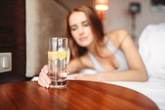 La mano femminile tiene il vetro con acqua del limone Fotografia Stock