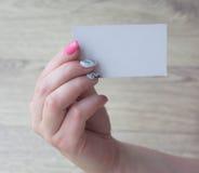 la mano femminile tiene la carta su un fondo fotografia stock