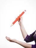 La mano femminile tiene la grande matita rossa Fotografie Stock Libere da Diritti