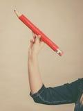 La mano femminile tiene la grande matita rossa Fotografia Stock