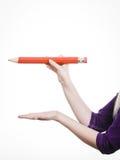 La mano femminile tiene la grande matita rossa Immagini Stock Libere da Diritti