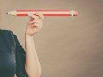 La mano femminile tiene la grande matita rossa Fotografia Stock Libera da Diritti