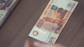 La mano femminile tocca cinque mila banconote della rublo sulla tavola archivi video