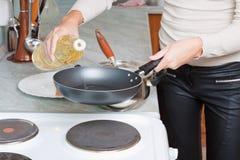 La mano femminile versa l'olio sulla vaschetta di frittura Fotografie Stock Libere da Diritti