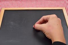 La mano femminile vuole scrivere qualcosa sulla lavagna con gesso Fotografia Stock Libera da Diritti