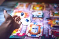 La mano getta i dadi sui precedenti dei giochi da tavolo Immagine Stock