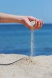 La mano getta la sabbia immagine stock libera da diritti