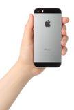 La mano giudica lo spazio di iPhone 5s grigio su fondo bianco Fotografia Stock